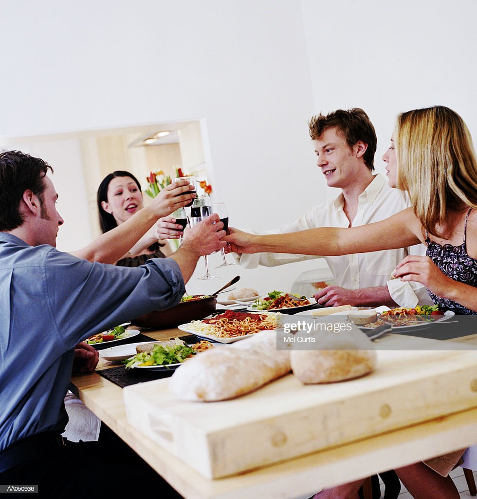 Two couples toasting wine glasses over dinner table : Stock Photo