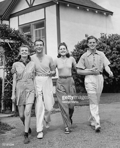 Two couples walking on lawn in front of house (B&W)