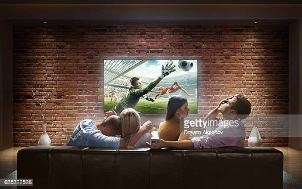 Two couples watching Soccer game at home