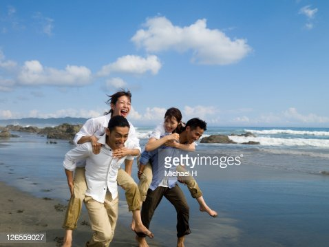 Two couples who compete happily on a beach : Stock Photo