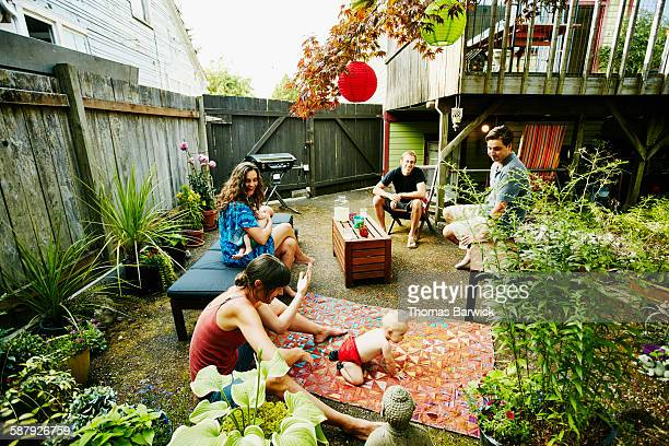 Two couples with babies gathered on patio of home