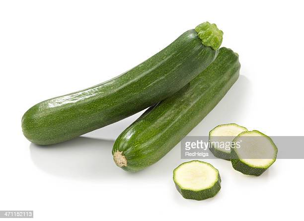 Two courgettes stacked with three slices beside them