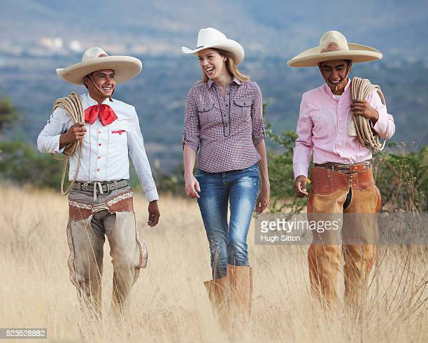 Two cowboys and woman walking through field