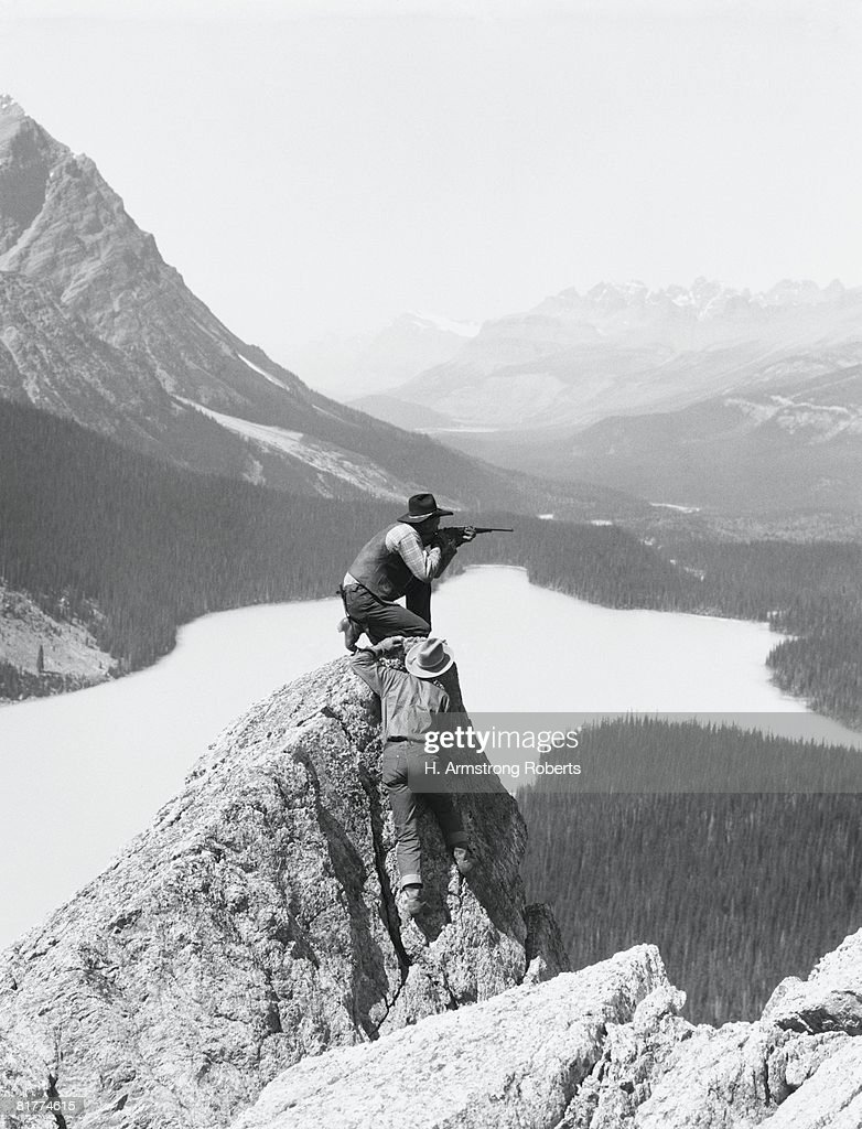 Two cowboys on top of rocky crag, one man kneeling, aiming hunting rifle, Bow Lake, Alberta, Canada. : Stock Photo