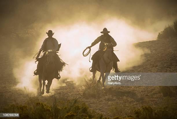 Two Cowboys Racing Through Desert on Horseback