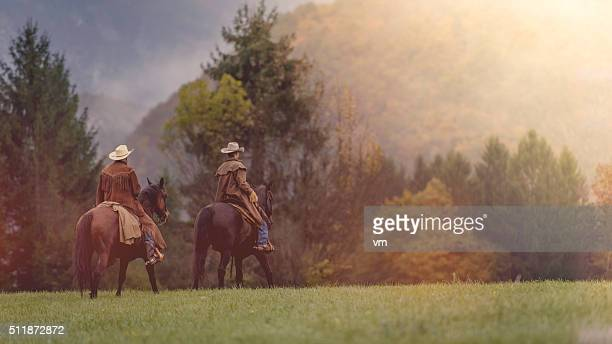Two cowboys riding across a field in a forest