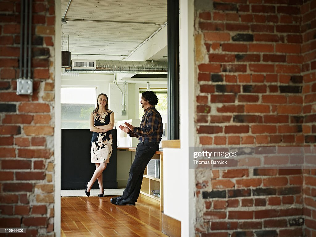 Two coworkers in discussion in office lobby : Stock Photo