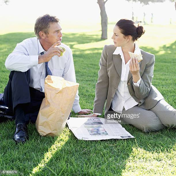Two co-workers sitting in a lawn and eating lunch from a brown paper bag
