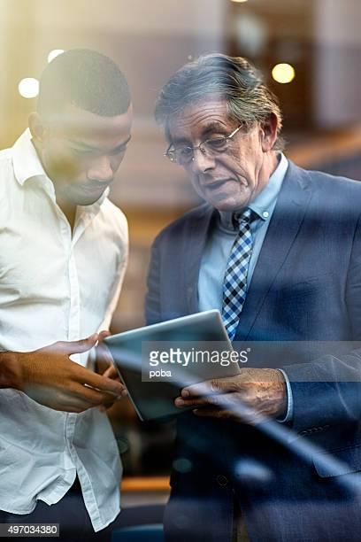 Zwei Kollegen, die mit einem digitalen tablet im Büro
