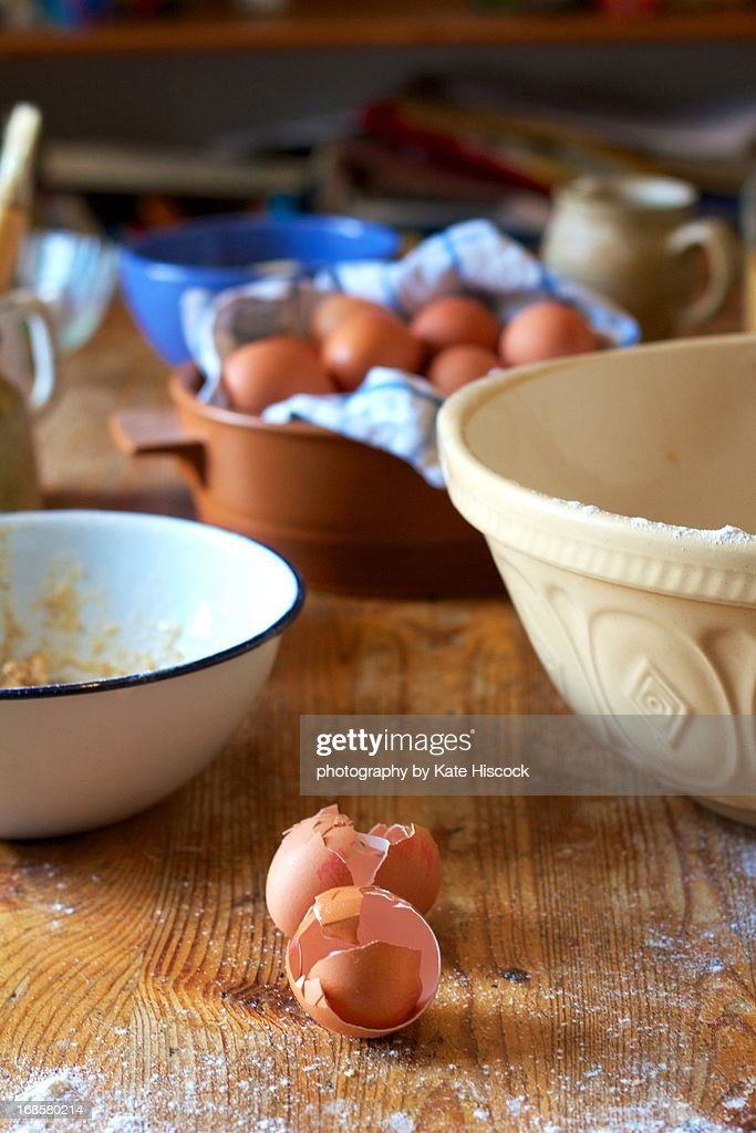 Two cracked egg shells on a messy kitchen table : Stock Photo