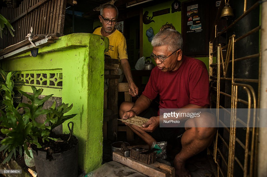 Two craftsman make copper brass handicrafts in Kota Gede, Yogyakarta, Indonesia, on May 4, 2016. Crafters can make ornament copper handicrafts into necklaces, bracelets, rings and other ornaments with price IDR. 100,000 - IDR. 300,0000 appropriate motif and size