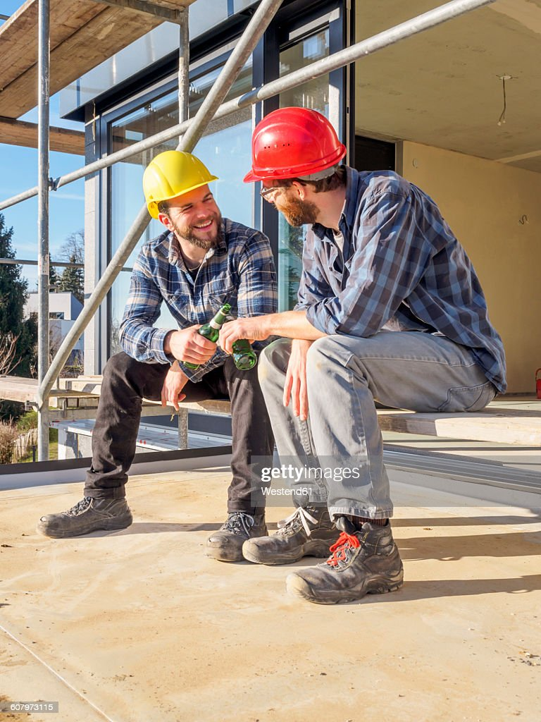 Two craftsmen clinking beer bottles in construction site : Stock Photo
