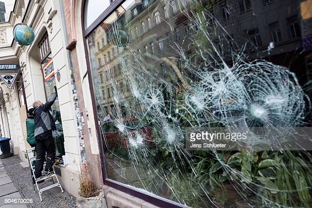 Two craftsmen repair the shattered windows of a clothing store the day after rightwing supporters rioted on January 12 2016 in Leipzig Germany...