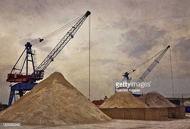 Two Cranes in port with sand mountains