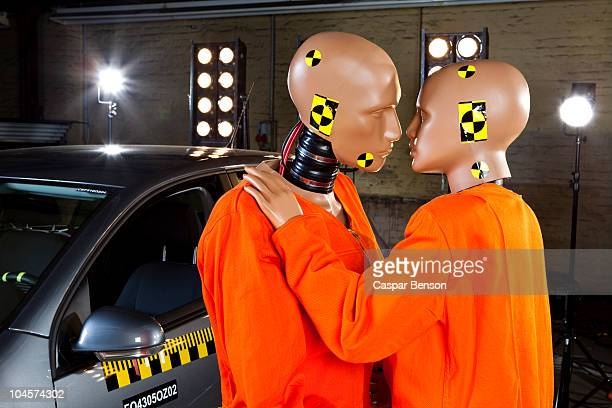 Two crash test dummies next to a car in a crash test laboratory about to kiss