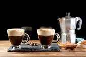 two cup of coffee, Italian coffee maker, coffee beans, cinnamon, napkin and brown sugar bowl on wood table and black background