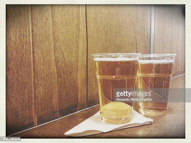 Two Cups Of Beer And Folded Napkin On Wooden Counter