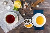 Two cups of black and green tea with cane and white sugar cubes on wooden rustic table with lemon, mint leaves, dried tea leaves, honey. Top view.