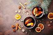 Two cups of christmas mulled wine or gluhwein with spices and orange slices on rustic table top view. Traditional drink on winter holiday. Flat lay.