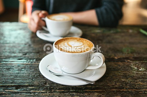Two cups of coffee on a wooden table, the girl holds in her hand one cup of coffee in the background. A photo indicates a meeting of people and a joint pastime. : Stock Photo