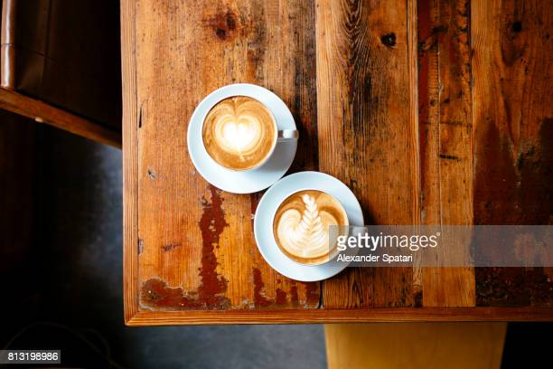 Two cups of coffee with foam latte art on a wooden table seen from above