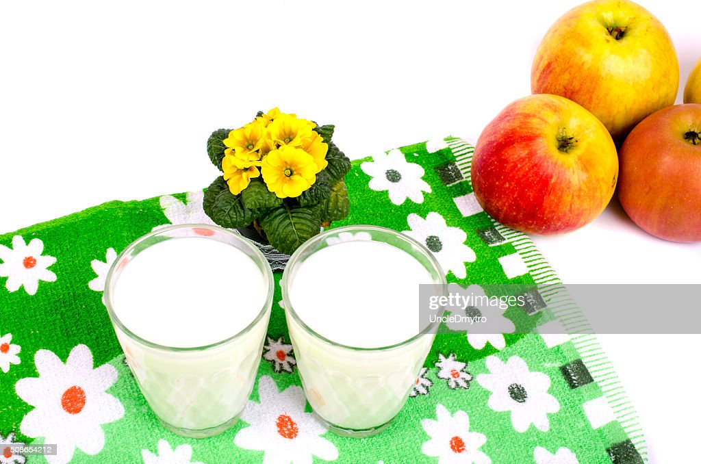 Two cups of milk, apples and flowers. : Stock Photo