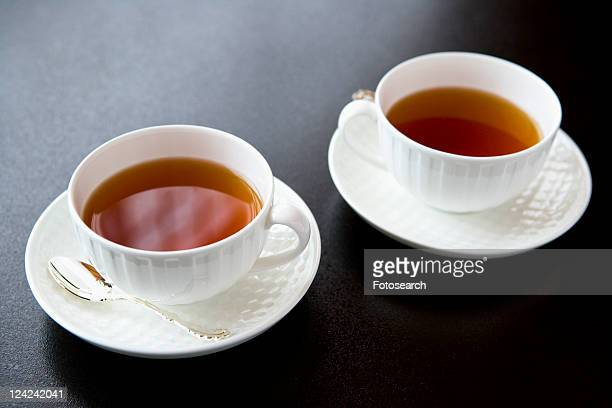 Two cups of tea, high angle view, black background