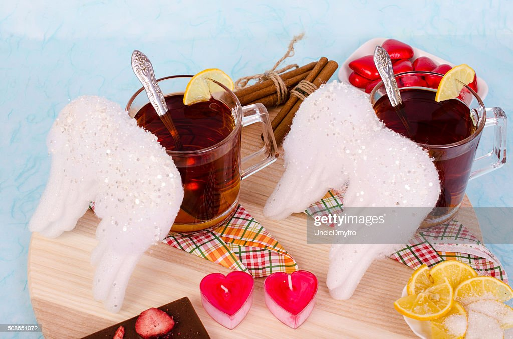 Two cups of tea, white wings and candles. : Stock Photo