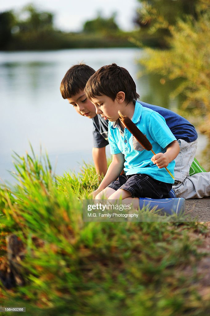 Two curious boys exploring a lake : Stock Photo