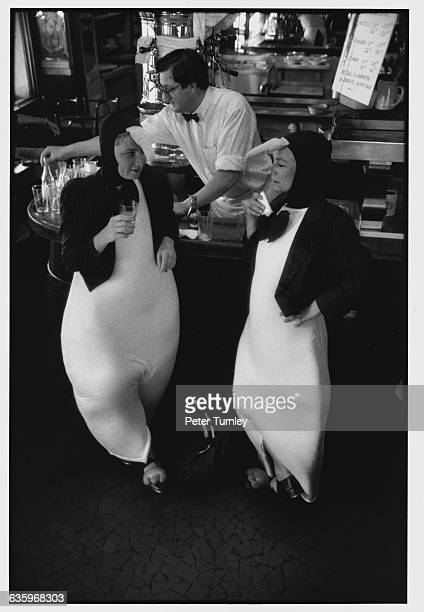 Two customers dressed as penguins have a drink at the bar of the Brasserie de l'Ile St Louis