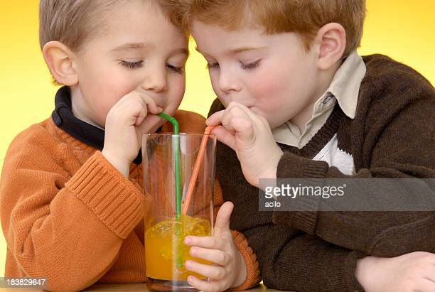 Two cute boys are making bubbles with orange lemonade