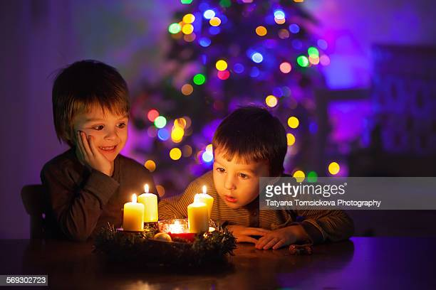 Two cute boys, watching candles burning