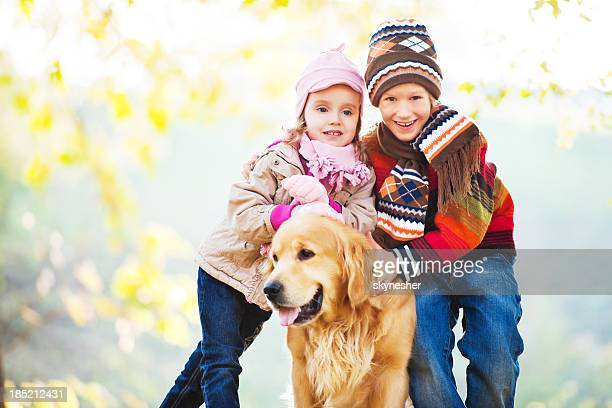 Two cute children enjoying in the park with their dog.