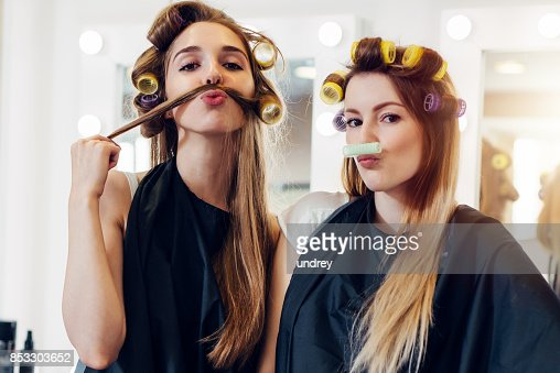 Two cute girlfriends in black cape wearing curlers making moustache out of their hair and roller in hairdressing salon : Stock Photo