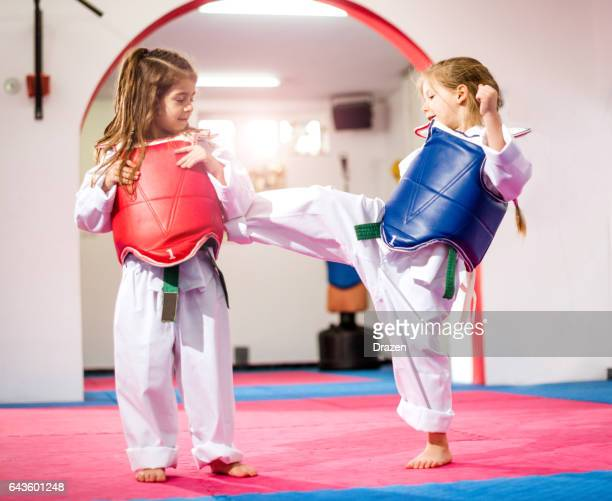 Two cute girls on taekwondo training, kicking and learning self-defence