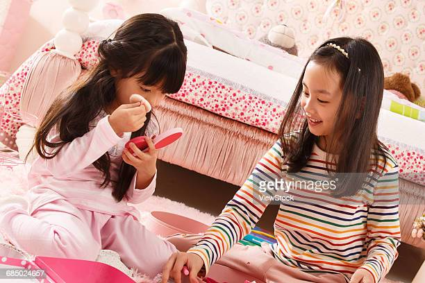 Two cute little girls play in the bedroom