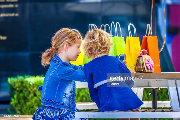 Two cute little girls with shopping bags in city