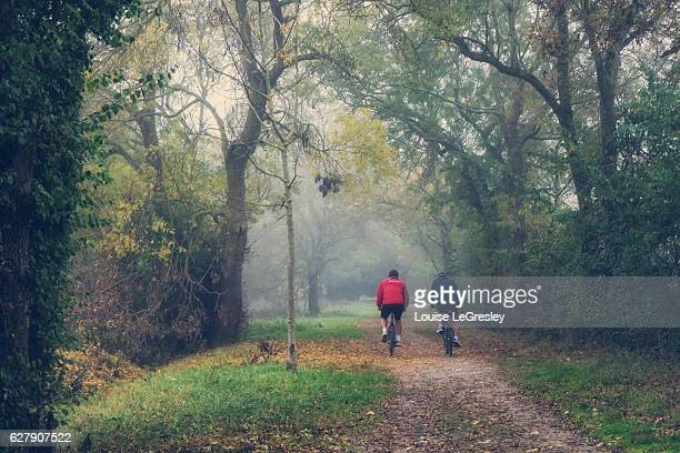 Two cyclist on a beautiful foggy autumn morning