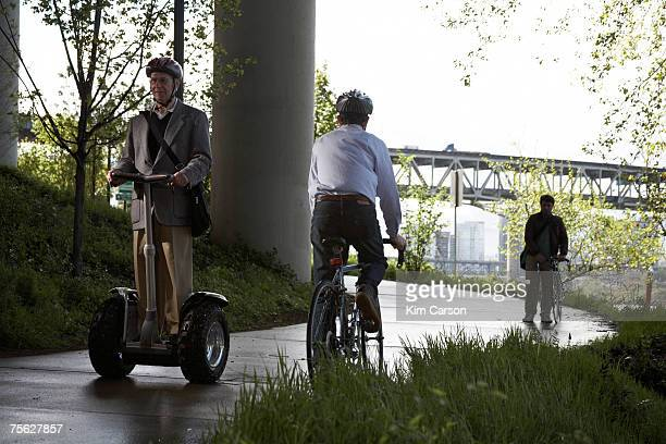Two cyclists and one man riding segway on path