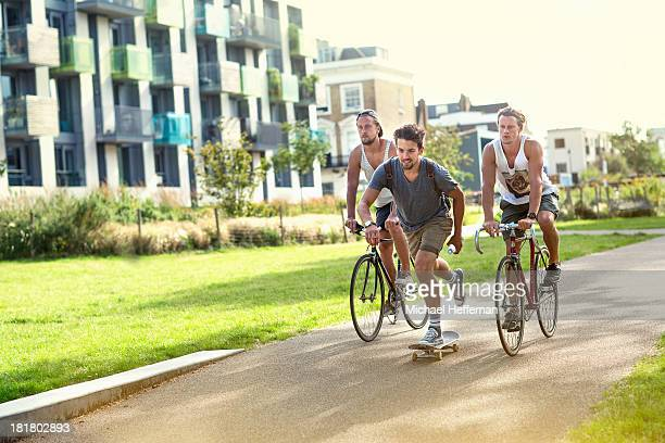two cyclists and one skateboarder in park