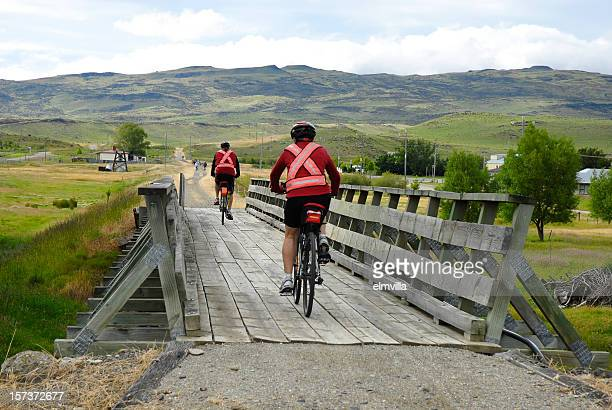 Two cyclists crossing a wooden railway bridge