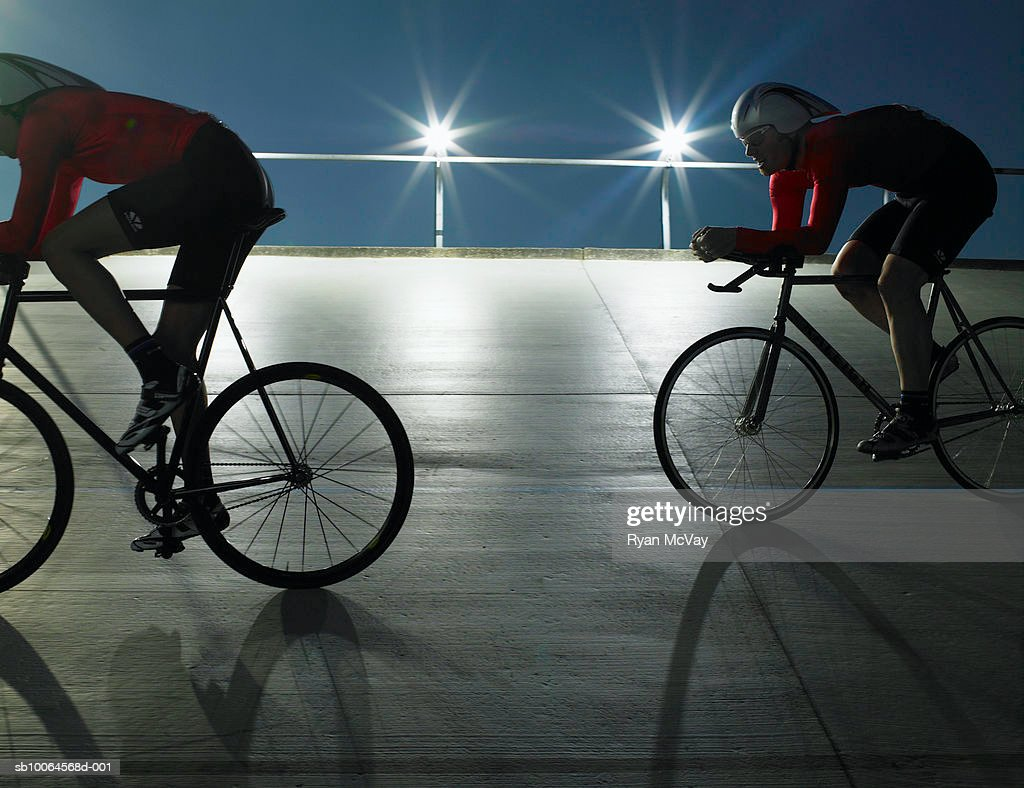 Two cyclists in action on velodrome track at night