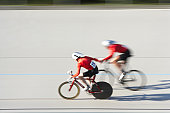 Two cyclists in action on velodrome track