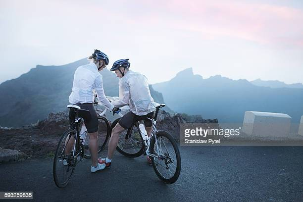 Two cyclists looking at map in mountains