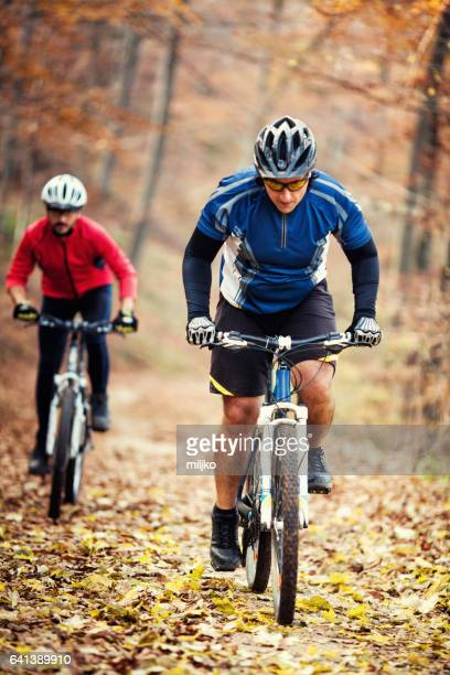 Two cyclists racing in forest at autumn