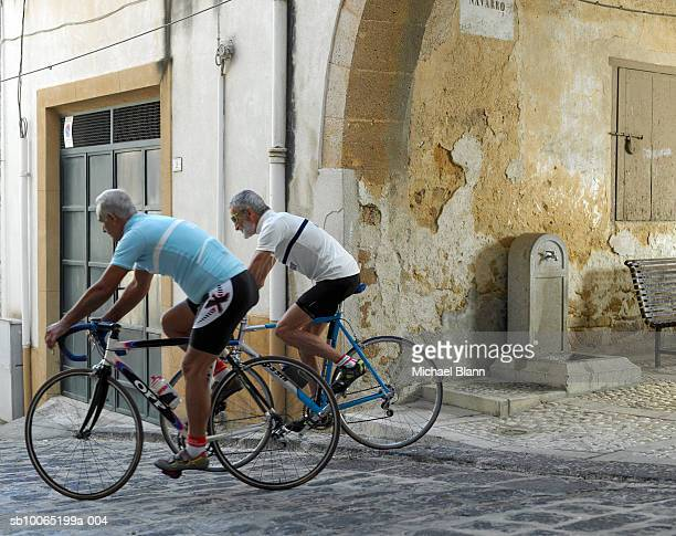 Two cyclists riding in old town
