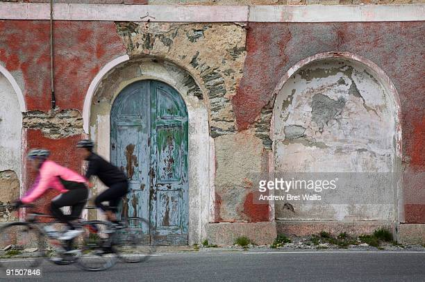 Two cyclists speeding past a derelict building