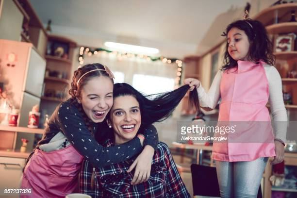 Two Daughters Making Fun with Their Mother in the Kitchen