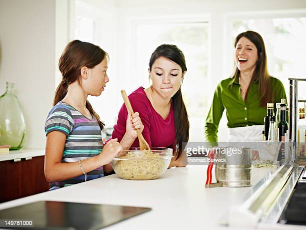 Two daughters mixing cookie dough in kitchen