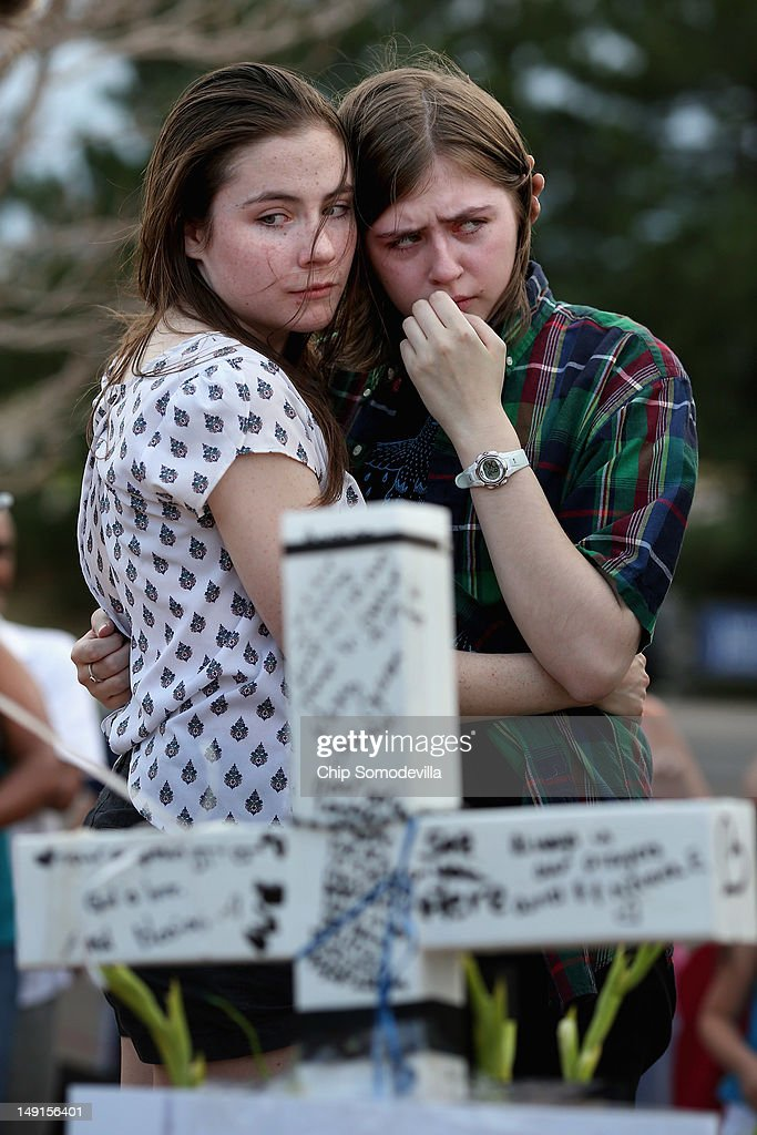 Two daughters of movie-theater-shooting-victim Gordon Cowden's embrace one another at the makeshift memorial built across the street from the Century 16 theater July 23, 2012 in Aurora, Colorado. Two of Cowden's teenage daughters were with him in the theater when he was killed. Twenty-four-year-old James Holmes is suspected of killing 12 and injuring 58 others Friday during a shooting rampage at a screening of 'The Dark Knight Rises.'
